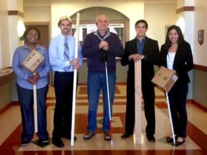 The intelligent white cane electrical engineering capstone team takes a break from testing the creation to pose alongside customer Terry Kebbel (Photo courtesy of Maryellen Kebbel)