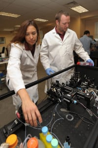 10/16/2015: NMSU chemical engineering professor Jessica Houston, left, and NMSU biochemistry professor Kevin Houston demonstrate how they use their custom-built flow cytometer to evaluate cancer cell cultures. Jessica Houston and her research team developed the flow cytometer in her lab, which in turn is used by Kevin Houston to conduct research in his cancer cell biochemistry lab. (Photo by Darren Phillips)